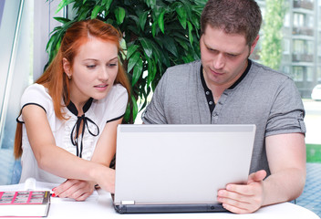 Male and female students studying using laptop