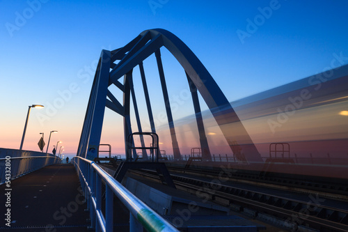 Train speeding over a bridge at dusk.