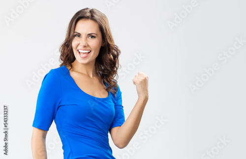 Happy gesturing young woman, over grey