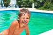 Smiling boy in the swimming pool on summer vacations