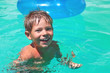 Smiling boy swims in pool on summer vacations