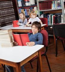 Schoolboy With Books Sitting At Library
