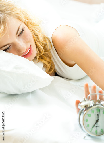 Blond beautiful woman with alarmclock
