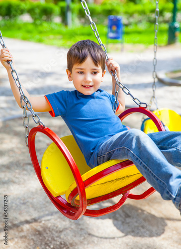 Joyful little boy swinging on a swing