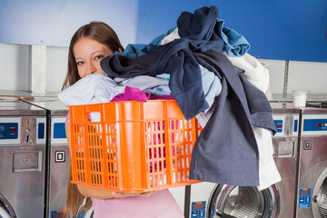 Woman Carrying Basket Full Of Dirty Clothes