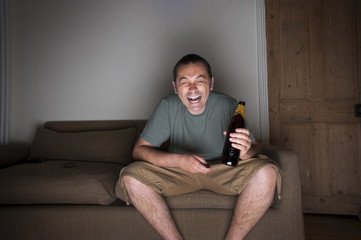 man drinking beer and laughing at the tv