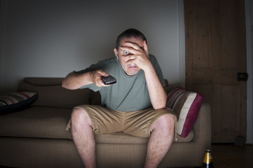 man covering his eyes watching tv