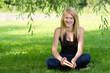 Lachender Teenie im Schatten eines Baumes mit Buch