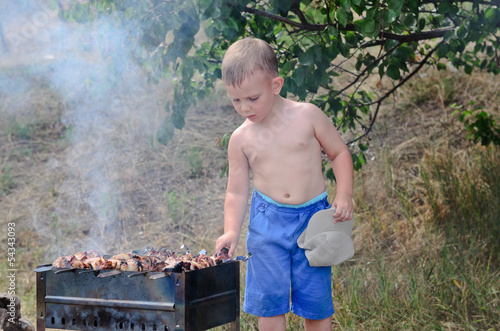 Little boy turning kebabs over the fire