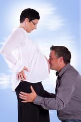 Papa küsst den Schwangerenbau von Mama