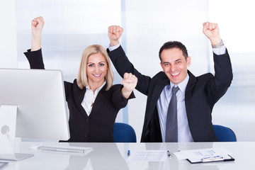Businessman And Businesswoman Raising Hand