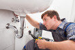 Young plumber fixing a sink in bathroom - 54345414