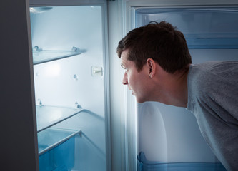 Hungry man looking in refrigerator