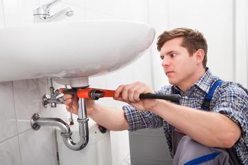 Portrait of male plumber fixing a sink