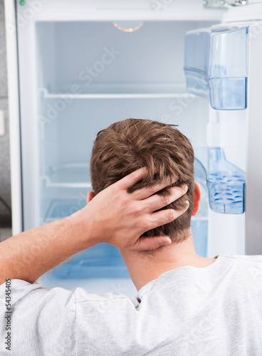 Thoughtful man looking in empty refrigerator