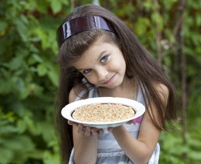 Little girl holding a plate with a white currants