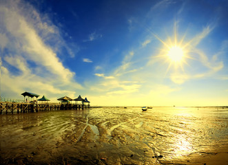 View of pier under bright sun at receding shore