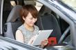 車でタブレットを見る女性 ビジネス