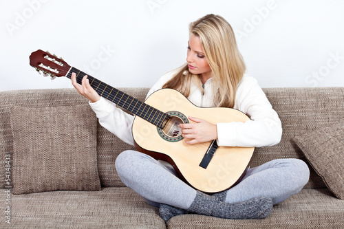 young woman practises playing the guitar