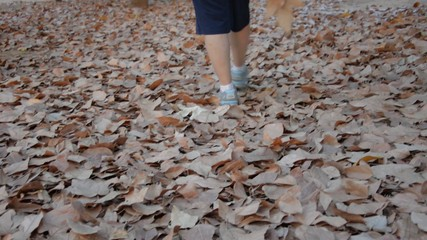 Lonely woman walking on leaf litter in the park