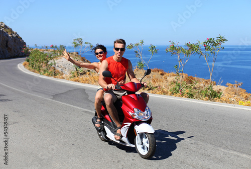 Happy young couple driving scooter on summer vacation