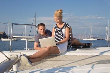 Junges Paar surft im Internet und schreibt e-mails am Segelboot