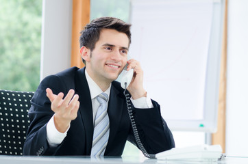 freundlicher geschäftsmann beim telefonieren