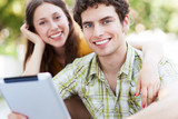 Young couple using digital tablet outdoors