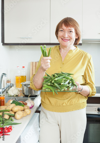 Smiling mature housewife cooking  vegetables
