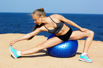 Young happy woman doing fitness exercises on the ball