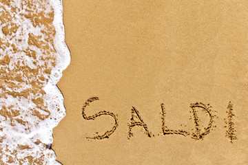 written saldi drawn on the sand