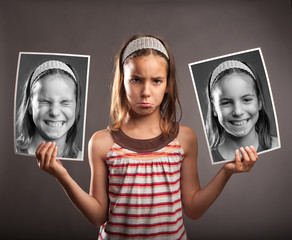 sad little girl holding two photos of herself