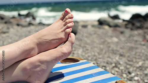 Female feet on sunbed by the sea