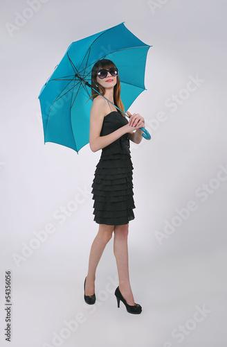девушка в чёрном платьи идёт под синим зонтом