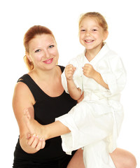 Mom teaches daughter dressed in a kimono karate kick insulated