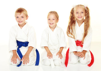 Cheerful young athletes sitting in a karate pose ritual