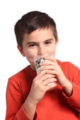 bambino beve un bicchiere di latte