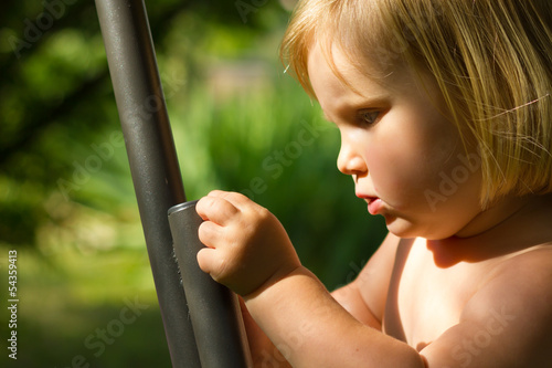Young child exploring and touching a metal bar in the garden