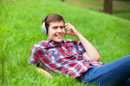 Handsome young man with headphones at green grass