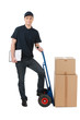 Box moving. Cheerful young deliveryman leaning on the cart with