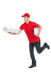 Hurrying to be in time. Cheerful young deliveryman running with