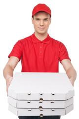 Here is your pizza! Cheerful young deliveryman stretching out a