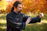 Man practicing Tai Chi in autumn park