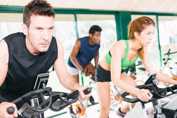 Three Friends Are In A Spinning Class At Gym