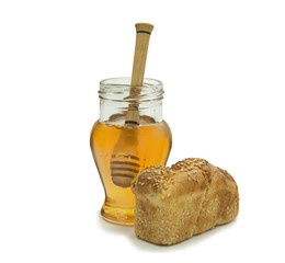 Jar of honey and loaf of bread on white background