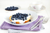Brioche or english muffin with blueberries and cream