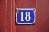 House Number Eighteen sign on red wooden panel