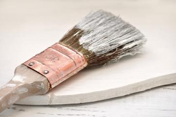 Pinsel mit weißer Farbe auf Holz