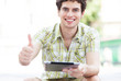 Man with digital tablet showing thumbs up