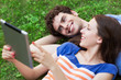 Couple using digital tablet on lawn